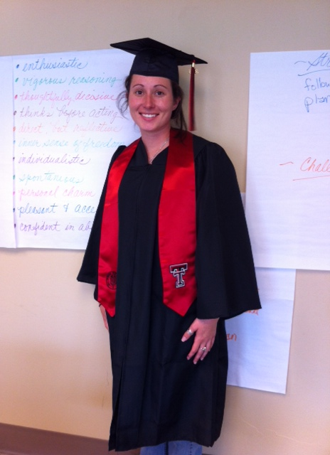 Ashley Franklin in cap and gown with strengths listed behind her on a large white sticky note