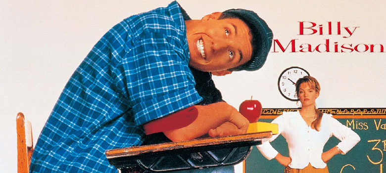 Picture of Billy Madison sitting at desk smiling while teacher looks at him. Movie Poster.