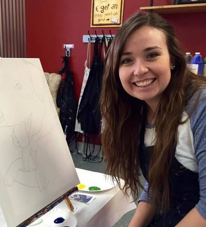 Hannah smiling with a painting canvas