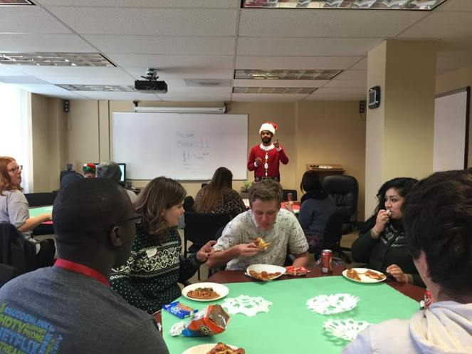 Tutor Appreciation Day. Dhweep in the background dressed as Bingo Santa while students and tutors enjoying pizza.