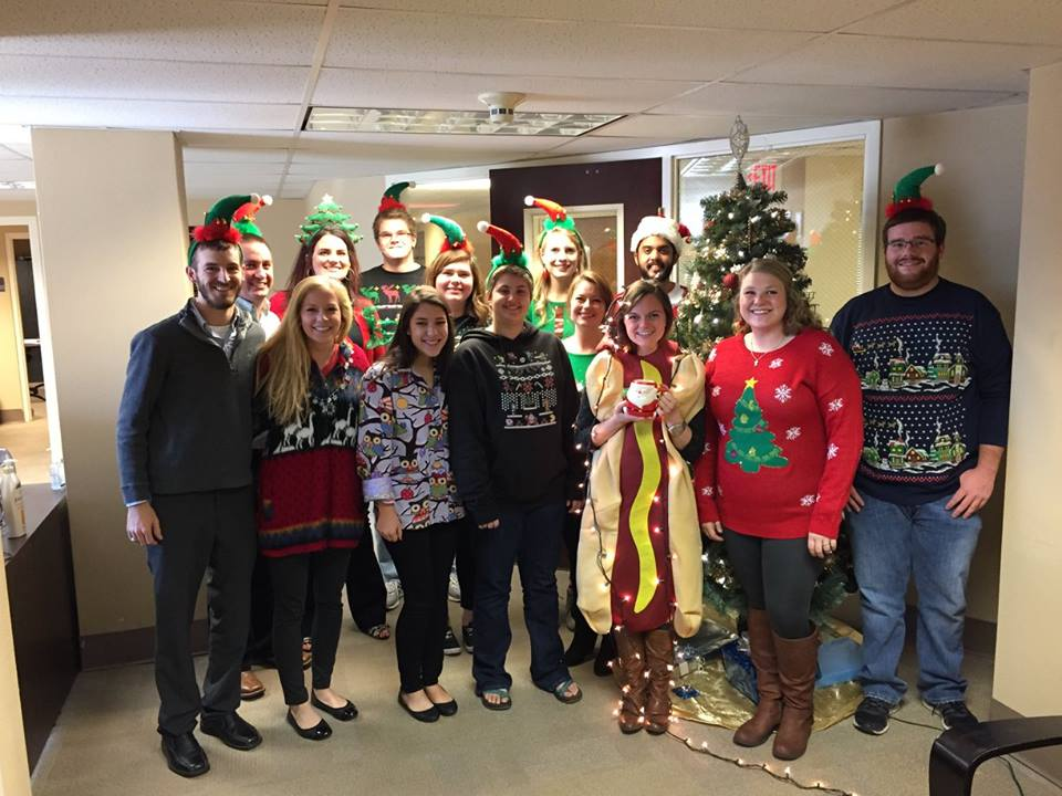 Counselors and Master Tutors smiling in ugly sweaters in front of the Christmas Tree