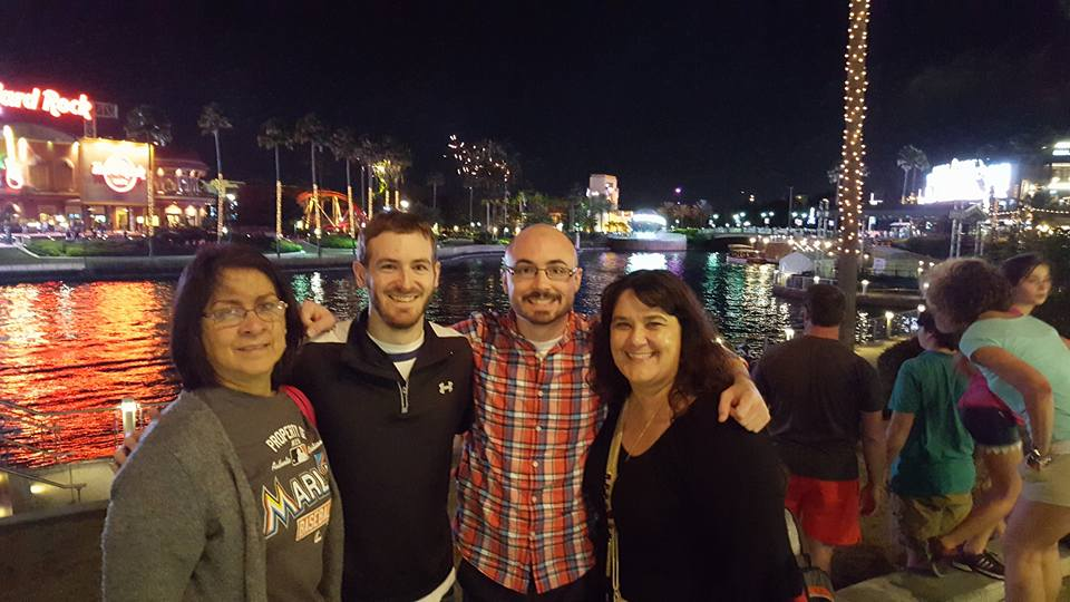 4 People smiling, standing in front of a river, with fireworks in background at night