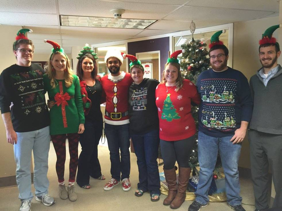 8 people in ugly christmas sweaters with their arms around each other