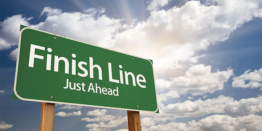 """A road sign that reads, """"Finish Line, Just Ahead"""" with blue sky, clouds, and the sun in the background"""