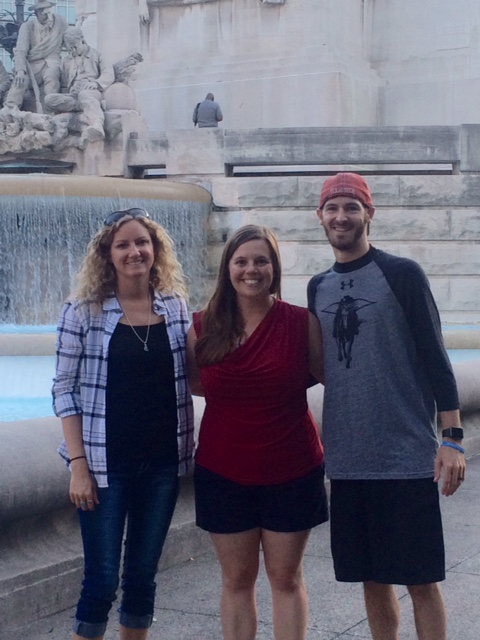 2 women and 1 man standing in front of a water fall monument, smiling