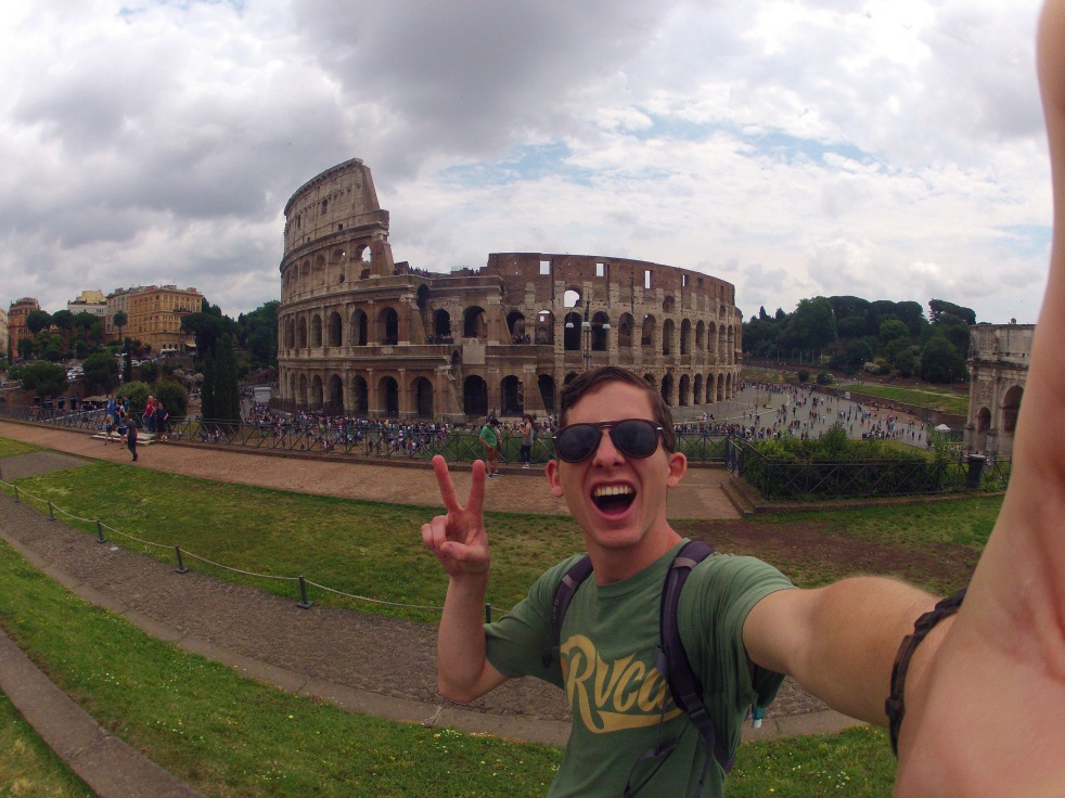 "A man standing in front of the Coliseum in Rome, holding two fingers up in a ""peace"" sign."