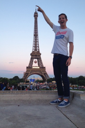 A young man smiles in front of the Eiffel Tower in Paris, France