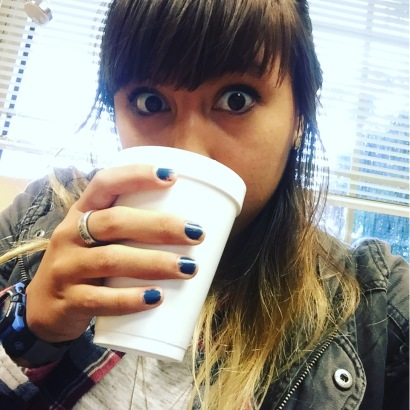 A woman drinking a cup of coffee with wide eyes