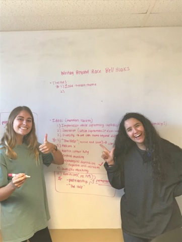 2 college-aged women stand in front of a whiteboard with writing notes for a class.