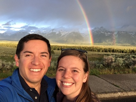 A selfie of a man and woman with a rainbow and mountains behind them