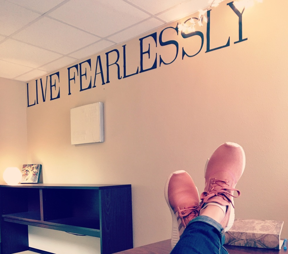 "A view of an office wall, with the words ""Live Fearlessly"" written on the wall in large letters"