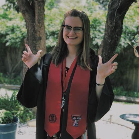 "A young woman smiles and holds her hands up in the ""Guns Up"" pose"
