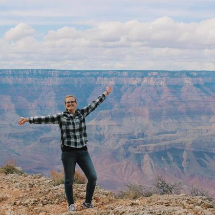 A young woman smiles and holds her arms out in front of the Grand Canyon