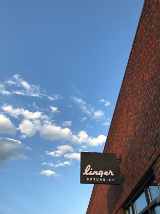 A photo of a blue sky with small white clouds, with a restaurant sign in the corner