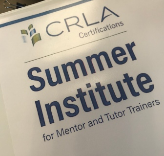 "A close up photo of a training manual entitled ""Summer Institute for Mentor and Tutor Trainers"""
