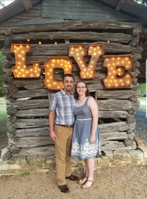 "A couple stand in front of a sign that says ""LOVE"""
