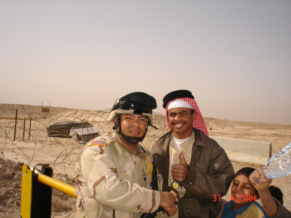 A young man in military gear shakes hands with a local iraqi man.